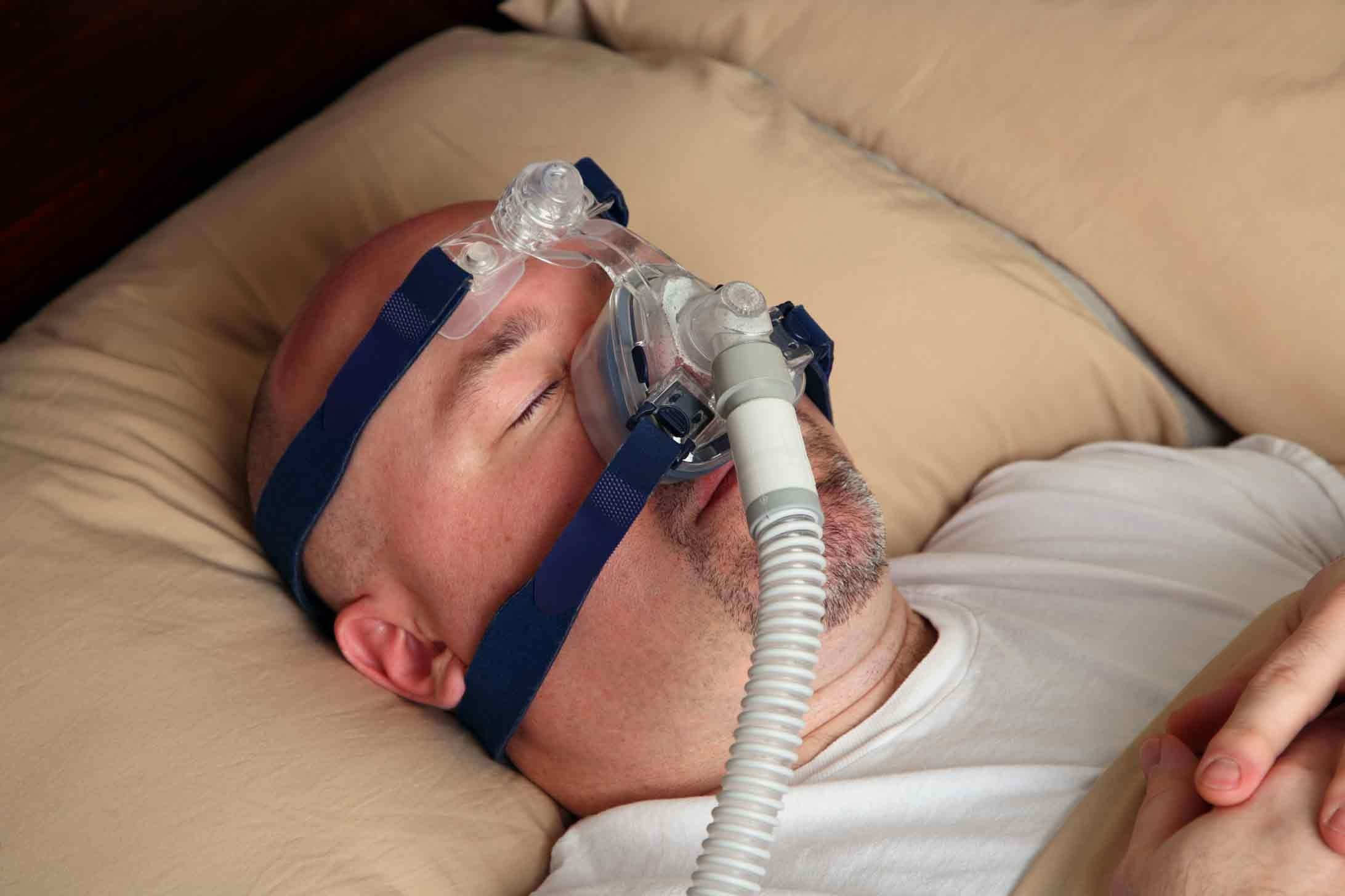 Man sleeping with a CPAP machine.